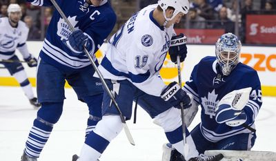 Toronto Maple Leafs goaltender Jonathan Bernier, right, puts his glove up to make a save as Dion Phaneuf (3) holds off Tampa Bay Lightning right winger B.J. Crombeen (19) during first period of an NHL game in Toronto, Tuesday, Jan. 28, 2014. (AP Photo/The Canadian Press, Frank Gunn)