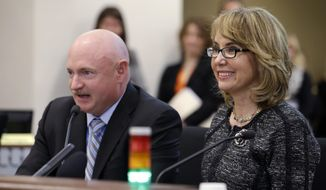"Former Arizona Congresswoman Gabrielle Giffords, right, smiles briefly as her husband, retired NASA space shuttle commander Mark Kelly, testifies before a Washington state House panel Tuesday, Jan. 28, 2014, in Olympia, Wash. Giffords, who survived a 2011 shooting, testified before the panel considering an initiative to expand firearm background checks in the state, telling lawmakers that ""the nation is counting on you."" With Kelly sitting next to her, Giffords spoke slowly and briefly to the panel that was taking public testimony on Initiative 594. (AP Photo/Elaine Thompson)"