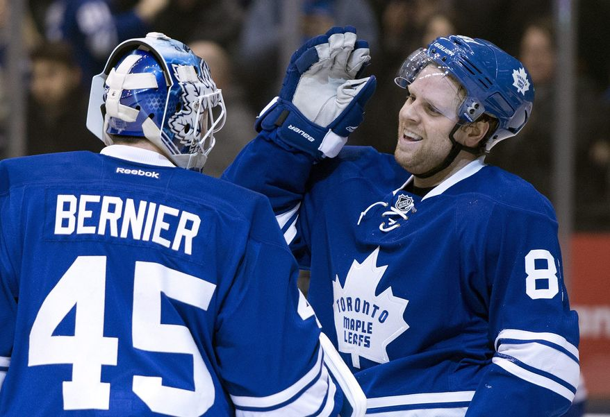Toronto Maple Leafs goaltender Jonathan Bernier, left, and Phil Kessel celebrate after an NHL hockey game against the Tampa Bay Lightning in Toronto, Tuesday, Jan. 28, 2014. (AP Photo/The Canadian Press, Frank Gunn)