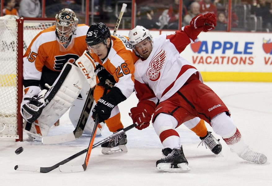 Philadelphia Flyers' Erik Gustafasson, center, takes Detroit Red Wings' Darren Helm, right, off the puck as goalie Steve Mason defends during the first period of an NHL hockey game, Tuesday, Jan. 28, 2014, in Philadelphia. (AP Photo/Tom Mihalek)
