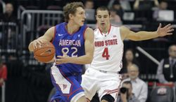 """FILE - This Nov. 20, 2103 file photo shows American University's John Schoof, left, guarded by Ohio State's Aaron Craft during the first half of an NCAA college basketball game in Columbus, Ohio. From Princeton to American by way of Georgetown with a guard named """"Peewee,"""" Mike Brennan has the Eagles unbeaten in the Patriot League in his first season at the school.  (AP Photo/Jay LaPrete, File) **FILE**"""