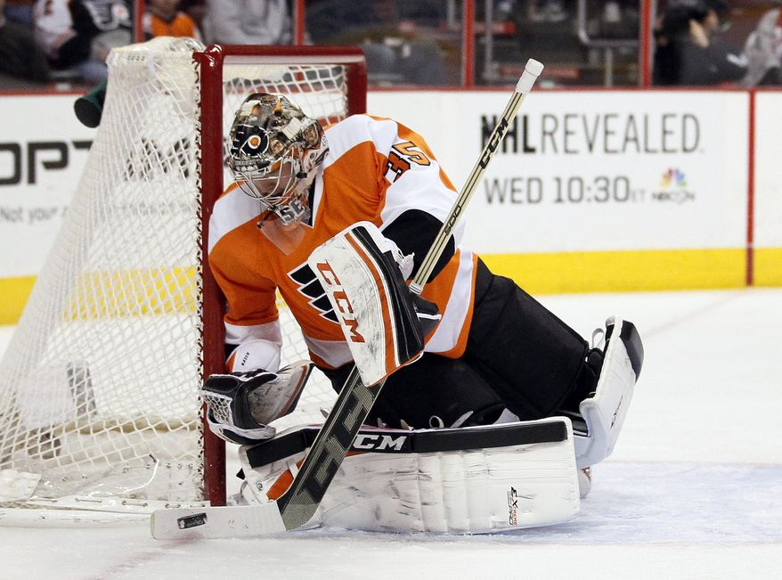 Philadelphia Flyers' Steve Mason sweeps away a shot on goal during the first period of an NHL hockey game against the Detroit Red Wings Tuesday, Jan. 28, 2014, in Philadelphia.  (AP Photo/Tom Mihalek)