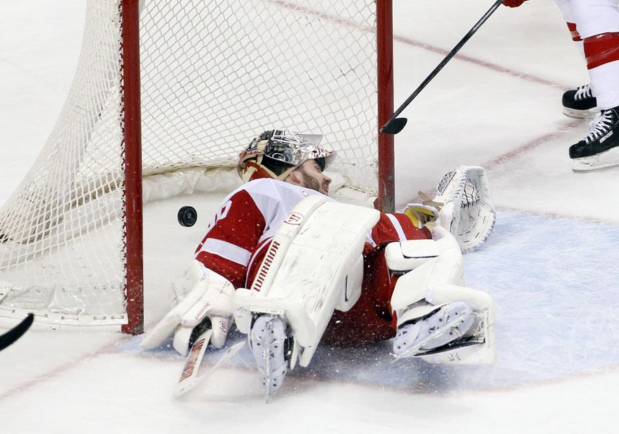 Detroit Red Wings goalie Jonas Gustavsson lays in the crease with the goal scored by Philadelphia Flyers' Sean Couturier behind him during the third period of an NHL hockey game, Tuesday, Jan. 28, 2014, in Philadelphia. The Flyers won 5-0. (AP Photo/Tom Mihalek)