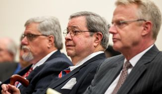 Tom Hensley, center, a lobbyist for the Wine and Spirits Wholesalers of Tennessee, listens to the discussion of the latest wine-in-supermarkets proposal during a House State Government Committee hearing in Nashville, Tenn., on Tuesday, Jan .28, 2014. At left is John New, a fellow lobbyist for the liquor wholesalers that have traditionally opposed the supermarket wine proposal. At right is Rep. Jon Lundberg, R-Bristol,  main sponsor of the measure to allow to allow wine to be sold in grocery and convenience stores. (AP Photo/Erik Schelzig)