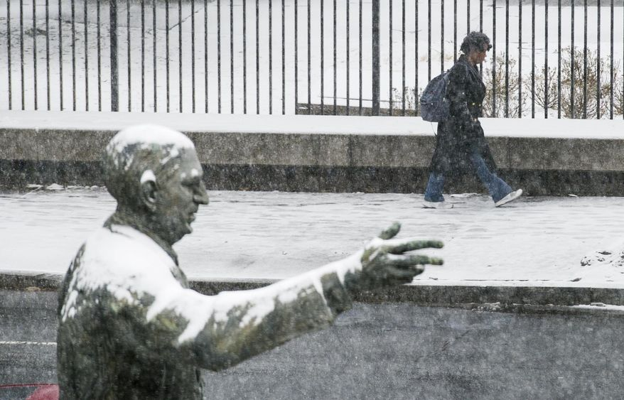The snow covered statue of late Georgia Governor and U.S. Sen.Richard B. Russell points the direction for a pedestrian as she makes her way past the state capitol while snow begins to accumulate Tuesday, Jan. 28, 2014, in Atlanta. (AP Photo/John Amis)