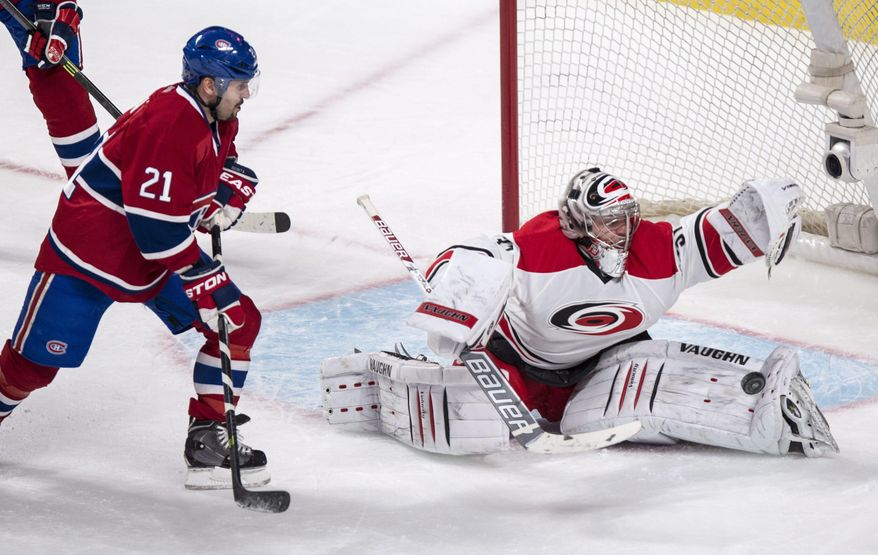 Carolina Hurricanes goalie Anton Khudobin makes a save off Montreal Canadiens' Brian Gionta during the second period of an NHL hockey game Tuesday, Jan. 28, 2014, in Montreal. (AP Photo/The Canadian Press, Paul Chiasson)