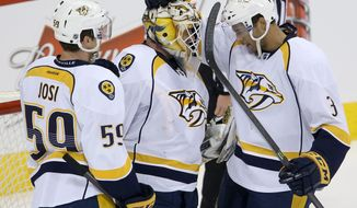 Nashville Predators' Roman Josi (59) and Seth Jones (3) congratulate goaltender Carter Hutton (30) after a 4-3 win over the Winnipeg Jets in an NHL hockey game Tuesday, Jan. 28, 2014, in Winnipeg, Manitoba. (AP Photo/The Canadian Press, Trevor Hagan)