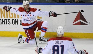 Washington Capitals defenseman Mike Green (52) celebrates his game winning goal with Dmitry Orlov (81) during the overtime session of an NHL hockey game against the Buffalo Sabres in Buffalo, N.Y., Tuesday, Jan. 28, 2014. Washington won 5-4. (AP Photo/Gary Wiepert)