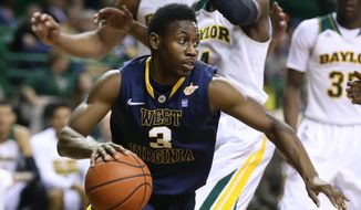 West Virginia guard Juwan Staten (3) drives past Baylor guard Gary Franklin (4) in the first half of an NCAA college basketball game, Tuesday, Jan. 28, 2014, in Waco, Texas. (AP Photo/Waco Tribune Herald, Rod Aydelotte)
