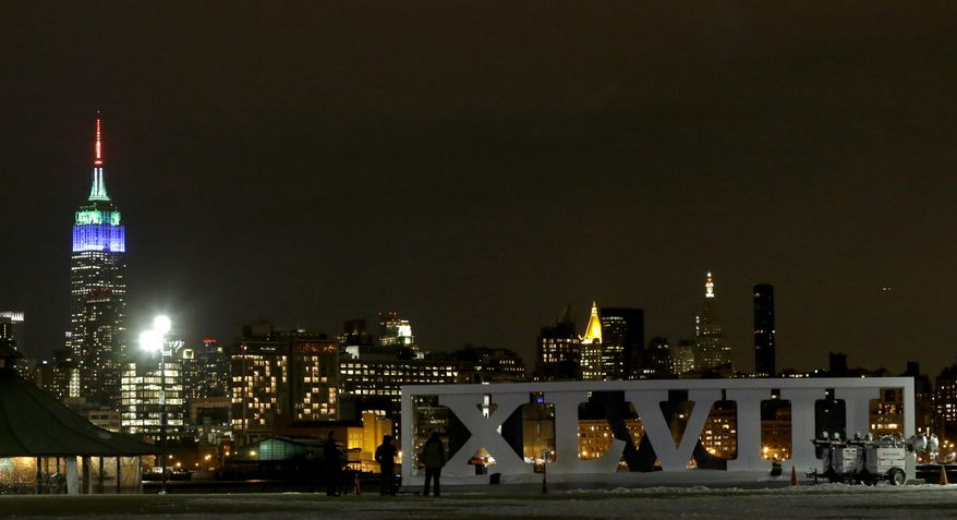 People watch fireworks as they stand near the Roman numerals for NFL Super Bowl XLVIII football game at Pier A Park in Hoboken, N.J., Monday, Jan. 27, 2014. The Seattle Seahawks and the Denver Broncos are scheduled to play in the Super Bowl on Sunday, Feb. 2 at MetLife Stadium in East Rutherford, N.J. The fireworks were part of a kick off event for the game. (AP Photo/Julio Cortez)