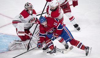 Carolina Hurricanes defenseman Andrej Sekera takes out Montreal Canadiens' Brendan Gallagher from in front of goalie Anton Khudobin during the third period of an NHL hockey game Tuesday, Jan. 28, 2014, in Montreal. Montreal won 3-0. (AP Photo/The Canadian Press, Paul Chiasson)