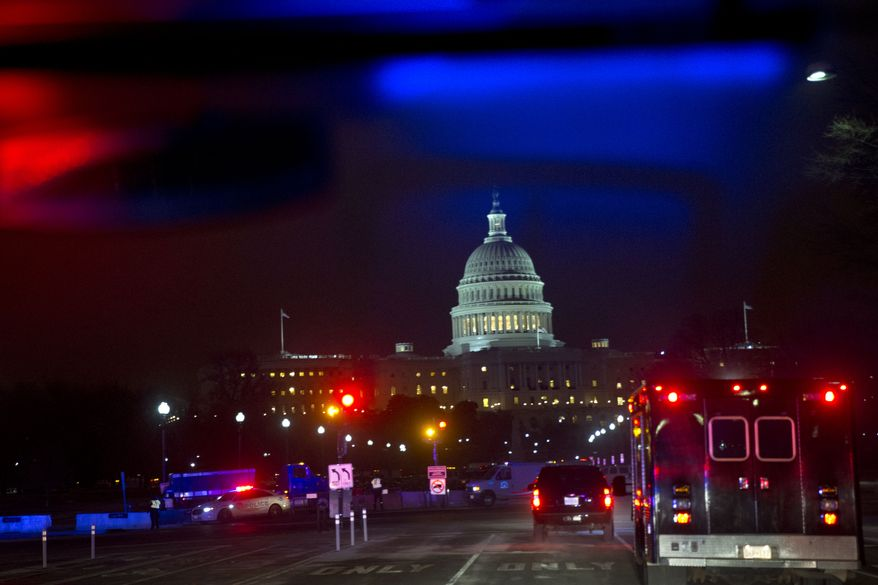 Police lights reflect as the motorcade carrying President Barack Obama to give his State of the Union speech arrives at the U.S. Capitol in Washington, Tuesday, Jan. 28, 2014. (AP Photo/Jacquelyn Martin)
