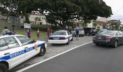 Police respond to the campus of Roosevelt Hight School, after a shooting, Tuesday, Jan. 28, 2014, in Honolulu.  A police officer shot a 17-year-old runaway in the wrist at the high school after the teen cut one officer with a knife and punched two others, authorities said.  State Department of Education spokeswoman Donalyn Dela Cruz said the boy showed up Tuesday morning at Roosevelt High School. Officials there recognized him as a runaway who was not registered for classes, and called police.  Maj. Richard Robinson, commander of the Honolulu Police Department's Criminal Investigations Division, said the boy lunged at officers who arrived at the public high school near downtown Honolulu and tried to take him into custody. (AP Photo/Marco Garcia)