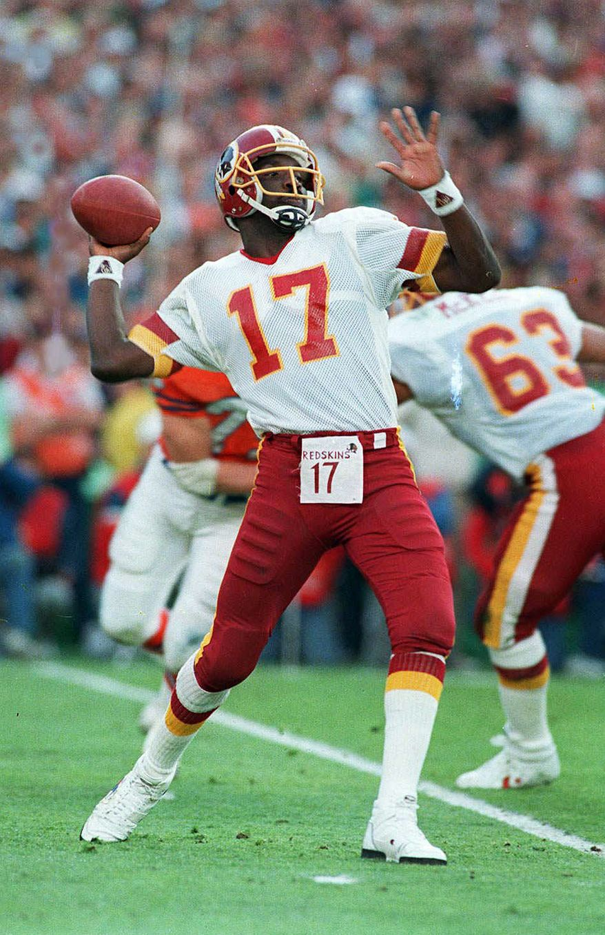 File-This Jan. 31, 1988, file photo shows Washington Redskins quarterback Doug Williams about to let go of a pass  during first quarter of Super Bowl XXII with the Denver Broncos in San Diego. Williams became the first black to start at quarterback in the Super Bowl, which prompted some awkward moments and a lasting urban legend from his session with reporters in San Diego. (AP Photo/Elise Amendola, File)