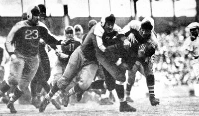 In this photo taken on Dec. 9, 1934, and released by the Pro Football Hall of Fame, Chicago Bears fullback Bronko Nagurski is tackled by New York Giants' Mel Hein during a Giants' 30-13 victory over the Bears in the NFL Championship game at the Polo Grounds in New York. (AP Photo/Pro Football Hall of Fame)