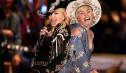 """Miley Cyrus performs with Madonna for MTV Tuesday Jan. 28, 2014. The 21-year-old pop star and the 55-year-old Queen of Pop grinded and grabbed each other as they performed Cyrus' hit """"We Can't Stop"""" and Madonna's 2000 track """"Don't Tell Me""""  Tuesday during a taping in Hollywood. The """"MTV Unplugged"""" special that closes with the duet is set to air Wednesday. (AP Photo/Sandy M. Cohen)"""