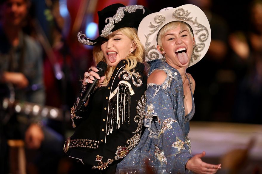 "Miley Cyrus performs with Madonna for MTV Tuesday Jan. 28, 2014. The 21-year-old pop star and the 55-year-old Queen of Pop grinded and grabbed each other as they performed Cyrus' hit ""We Can't Stop"" and Madonna's 2000 track ""Don't Tell Me""  Tuesday during a taping in Hollywood. The ""MTV Unplugged"" special that closes with the duet is set to air Wednesday. (AP Photo/Sandy M. Cohen)"