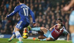 Chelsea's Mikel, at rear, slides in a tackle with West Ham's Mark Noble during the English Premier League soccer match between Chelsea and West Ham United at Stamford Bridge stadium in London, Wednesday, Jan. 29, 2014.(AP Photo/Alastair Grant)