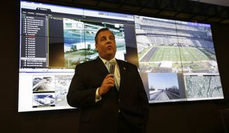 New Jersey Gov. Chris Christie speaks in front of large monitors as he visits the Super Bowl security operations center Wednesday, Jan. 29, 2014, in East Rutherford, N.J.  (AP Photo/Mel Evans,pool)