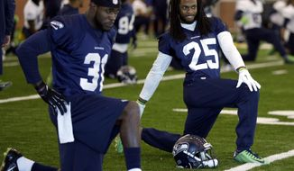 Seattle Seahawks safety Kam Chancellor, left, and cornerback Richard Sherman warm up with their teammates at the start of NFL football practice Wednesday, Jan. 29, 2014, in East Rutherford, N.J. The Seahawks and the Denver Broncos are scheduled to play in the Super Bowl XLVIII football game Sunday, Feb. 2, 2014. (AP Photo/Jeff Roberson)