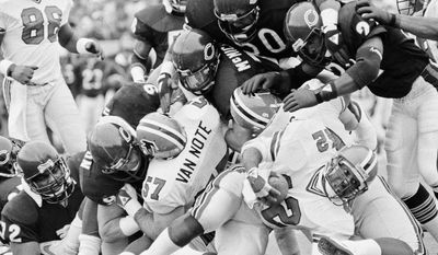 FILE - In this Nov. 24, 1985, file photo, Atlanta Falcons' Gerald Riggs (42) gets a dose of heavy coverage by Chicago Bears defenders Mike Singletary (50), Dave Duerson (22), and Steve McMichaels, during the first half of an NFL football game in Chicago. (AP Photo/Charlie Bennett, File)