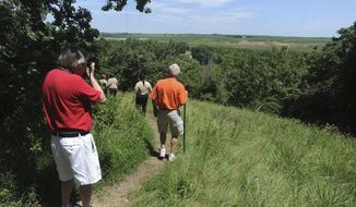 FILE - In this July 19, 2013 file photo, hikers explore Good Earth State Park at Blood Run in Lincoln County in Sioux Falls, S.D. Visitation and camping in South Dakota's state parks reached all-time highs in 2013 for the second year in a row. (AP Photo/Argus Leader, Jay Pickthorn, File) NO SALES