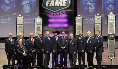 Twelve of the living members of the NASCAR Hall of Fame pose for the crowd at the end of the NASCAR Hall of Fame induction ceremony, Wednesday, Jan. 29, 2014, in Charlotte, N.C. From left are Leonard Wood, Junior Johnson, Dale Inman, Ned Jarrett, Dale Jarrett, Richard Petty, Bud Moore, Jack Ingram, Rusty Wallace, Bobby Allison and Darrell Waltrip; seated in front is Maurice Petty. (AP Photo/Bob Leverone)