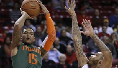 Miami guard Rion Brown, left, shoots over Maryland guard Roddy Peters during the first half of an NCAA college basketball game in College Park, Md., Wednesday, Jan. 29, 2014. (AP Photo/Patrick Semansky)
