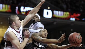 Cincinnati's Troy Caupain (10) passes the ball as he cuts between Temple's Dalton Pepper, left, and Anthony Lee during the second half of an NCAA college basketball game on Sunday, Jan. 26, 2014, in Philadelphia. Cincinnati won 80-76. (AP Photo/Michael Perez)