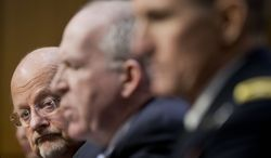 Director of National Intelligence James Clapper listens at left as CIA Director John Brennan, center, testifies on Capitol Hill in Washington, Wednesday, Jan. 29, 2014, before the Senate Intelligence Committee hearing on current and projected national security threats against the US. Defense Intelligence Agency Director Lt. Gen. Michael Flynn is at right. (AP Photo/Pablo Martinez Monsivais)