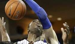 Central Florida's Isaiah Sykes (3) loses the ball as the arm of Memphis forward Austin Nichols reaches in to stop him from making a shot during the second half of an NCAA basketball game in Orlando, Fla., Wednesday, Jan. 29, 2014. Memphis won 69-59.(AP Photo/John Raoux)