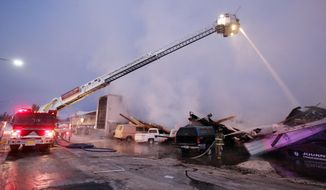 A ladder truck from The City of Fairbanks Fire Department sprays water on the remains of an apartment complex and second-hand furniture store on Geraghty Street in Fairbanks, Alaska on Wednesday morning, Jan. 29, 2014. The fire, which was reported shortly before 4 a.m., destroyed an 18-unit apartment complex. (AP Photo/Fairbanks Daily News-Miner, Eric Engman)
