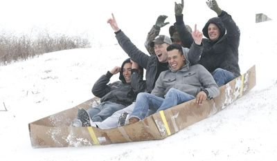 Kelvin Pena, 21, ; Matthew Bell, 22, ; Christopher Nunez, 19, ; Emanuel Austin, 24, from left, Marines assigned to 2d Battalion, 10th Marines, Camp Lejeune, Jacksonville,  move in their makeshift toboggan Wednesday afternoon, Jan. 29, 2014.  (AP Photo/The Daily News, John Althouse)