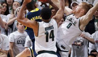 Michigan State's Russell Byrd (0) blocks a shot by Michigan's Glenn Robinson III as Michigan State's Gary Harris (14) defends during the second half of an NCAA college basketball game, Saturday, Jan. 25, 2014, in East Lansing, Mich. Michigan won 80-75. (AP Photo/Al Goldis)