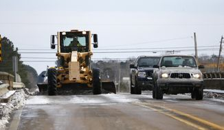 A Mississippi Department of Transportation road grader scrapes ice off the State Highway 27 railroad bridge in Crystal Springs while traffic drives past Wednesday, Jan. 29, 2014. Although warmer temperatures allowed the ice and sleet in some areas to begin to melt, many of the southern counties were under cloud cover for most of the day and temperatures stayed for the most part below freezing. (AP Photo/Rogelio V. Solis)