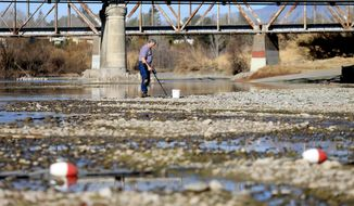 File - In this Jan. 14, 2014 file photo, Hugh Beggs of Santa Rosa, Calif., searches for coins in the middle of the Russian River at Healdsburg Veterans Memorial Beach in Healdsburg, Calif., taking advantage of the way below normal river flow. Seventeen rural communities in drought-stricken California are in danger of running out of water within four months, according to a list compiled by state officials. Wells are running dry or reservoirs are nearly empty in some communities. Others have long-running problems that predate the drought. The communities range from the area covered by the tiny Lompico County Water District in Santa Cruz County to the cities of Healdsburg and Cloverdale in Sonoma County. (AP Photo/ Santa Rosa Press Democrat, Kent Porter, File)