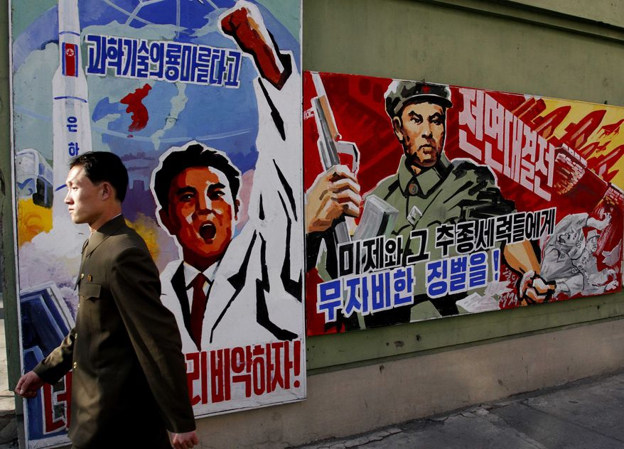 """FILE - In this March 26, 2013 file photo, a North Korean man walks past propaganda posters in Pyongyang, North Korea, that threaten punishment to the """"U.S. imperialists and their allies.""""  North Korea's propaganda machine is churning out near-daily diatribes against the United States and South Korea for a series of soon-to-start military maneuvers, warning nuclear war could be imminent and saying it will take dramatic action of its own if further provoked. (AP Photo/Kim Kwang Hyon, File)"""