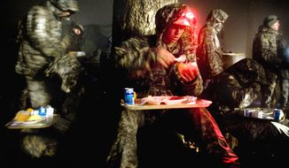 U.S. Army Rangers find a place to eat their first hot meal in days while tolerating the rain during mountaineering training. US Army photo