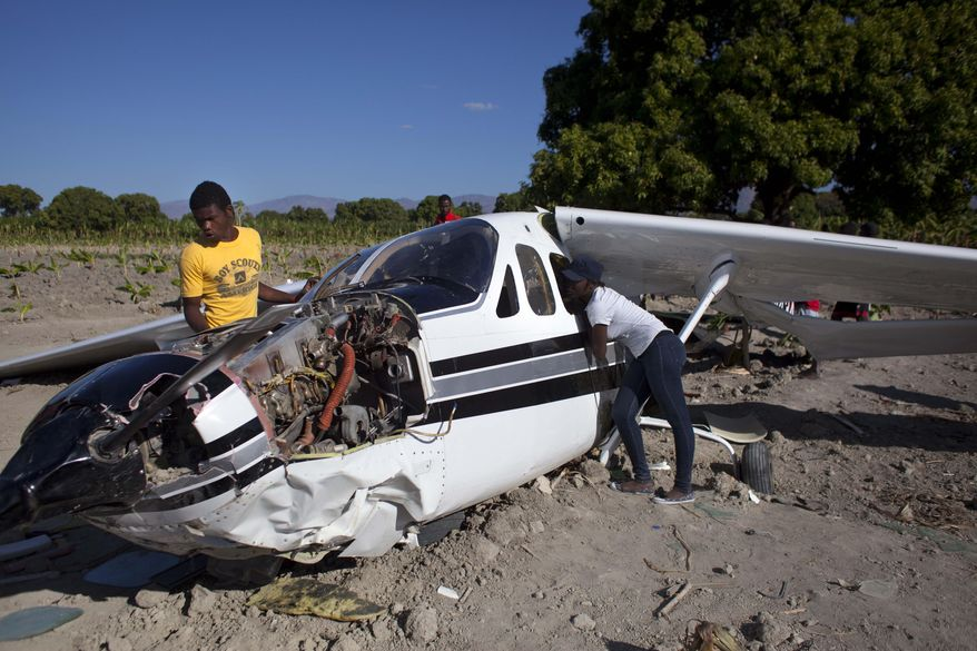 Residents check out a Cessna Super Skymaster that made an emergency landing the night before in a field just outside Cabaret, a coastal town northwest of Port-au-Prince, Haiti, Thursday Jan. 30, 2014. Haitian police said on Thursday that the small plane piloted by a U.S. citizen suffered mechanical problems and made an emergency landing in the banana field. Police inspector Joachin Antoine said that pilot Practor Antoine was treated for unspecified injuries at a hospital in the capital. A passenger named John Michael was not injured. (AP Photo/Dieu Nalio Chery)
