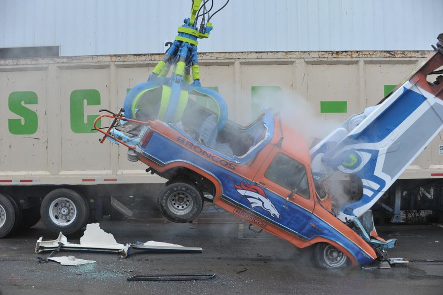 Seahawk fans at Scrap-It, a recycling business in Ferndale, Wa., destroy a 1985 Ford Bronco, painted in Denver Bronco colors, Wednesday, Jan. 29, 2014.  Crane operator Herb Parks says it was very satisfying and made him feel like he was part of the team. (AP Photo/The Bellingham Herald, Philip A. Dwyer)