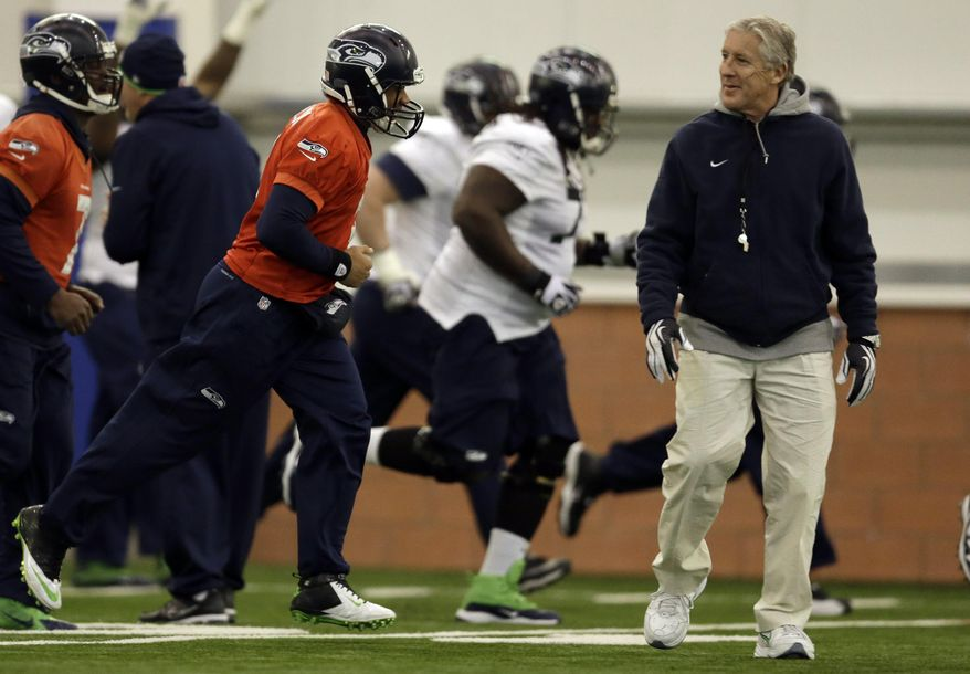 Seattle Seahawks head coach Pete Carroll, right, watches as quarterback Russell Wilson, left, and the rest of the team warms up during NFL football practice Thursday, Jan. 30, 2014, in East Rutherford, N.J. The Seahawks and the Denver Broncos are scheduled to play in the Super Bowl XLVIII football game Sunday, Feb. 2, 2014. (AP Photo)
