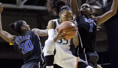 Miami Hurricanes guard Suriya McGuire (33) goes to the basket as Duke Blue Devils forward/center Amber Henson (30) and forward/center Elizabeth Williams (1) defend during the first half of an NCAA college basketball game in Coral Gables, Fla., Thursday, Jan. 30, 2014. (AP Photo)