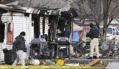Kentucky State Police fire investigators at the scene of an early morning blaze Thursday Jan. 30, 2014, at a home in Greenville, Ky., where nine people are presumed dead.  Remains of six people were found and three people are missing.  (AP Photo/The Gleaner, Mike Lawrence)