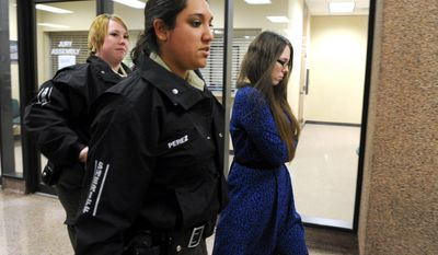 In this photo from Jan. 27, 2014, escorted by sheriff's deputies, Tiffany Klapheke, right, leaves the jury selection room at the Taylor County Courthouse in Abilene, Texas. Klapheke is charged with injury to a child in the August 2012 death of her 22-month-old daughter, Tamryn Klapheke, who died of malnutrition and dehydration. (AP Photo/Abilene Reporter-News, Nellie Doneva)