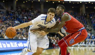 Creighton forward Doug McDermott, left, dribbles to the basket as St. John's forward Jakarr Sampson (14) guards during the second half of an NCAA college basketball game in Omaha, Neb., Tuesday, Jan. 28, 2014. (AP Photo/John Peterson)