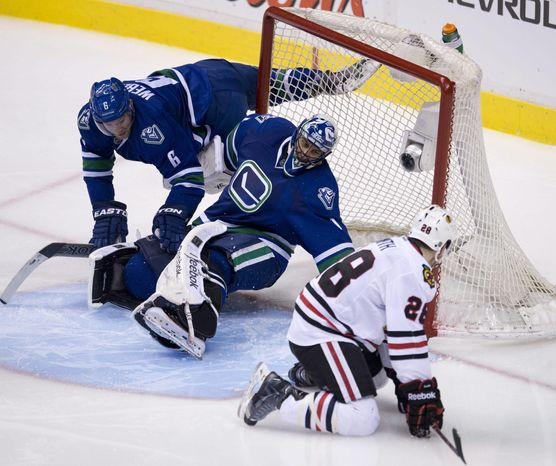 Vancouver Canucks defenceman Yannick Weber (6) looks on as Chicago Blackhawks right wing Ben Smith (28) tries to get a shot past Vancouver Canucks goalie Roberto Luongo (1)during the third period of NHL action in Vancouver, British Columbia Wednesday, Jan. 29, 2014. (AP Photo/The Canadian Press, Jonathan Hayward)