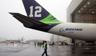 A Boeing 747-8 freighter, painted in Seattle Seahawks livery, is revealed at Boeing's Paine Field Wednesday, Jan. 29, 2014, in Everett, Wash. (AP Photo/The Herald, Sofia Jaramillo)