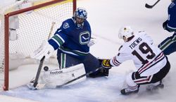 Chicago Blackhawks center Jonathan Toews (19) puts a shot past Vancouver Canucks goalie Roberto Luongo (1)during the second period of NHL action in Vancouver, British Columbia Wednesday, Jan. 29, 2014. (AP Photo/The Canadian Press, Jonathan Hayward)
