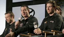 Driver Kyle Busch, center, answers a question as teammates Denny Hamlin, right, and Matt Kenseth, left, listen during a news conference at the NASCAR Sprint Cup auto racing Media Tour in Charlotte, N.C., Thursday, Jan. 30, 2014. (AP Photo)