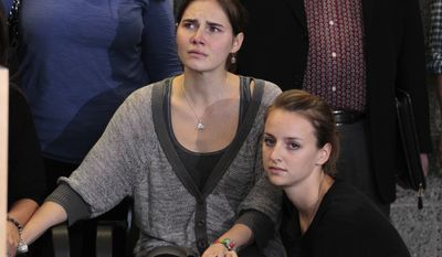 Amanda Knox, left, is comforted by her sister, Deanna Knox, during a news conference shortly after her arrival at Seattle-Tacoma International Airport Tuesday, Oct. 4, 2011, in Seattle. It's been four years since the University of Washington student left for the study abroad program in Perugia and landed in prison. The group Friends of Amanda Knox and others have been awaiting her return since an Italian appeals court on Monday overturned her conviction of sexually assaulting and killing her British roommate, Meredith Kercher. (AP Photo/Elaine Thompson)